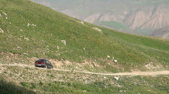 Russian Lada drives through Kyrgyz mountains Stock Footage