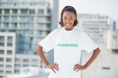 Smiling woman with hands on hips wearing volunteer tshirt - stock photo