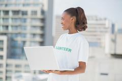 Cheerful pretty volunteer holding laptop Stock Photos