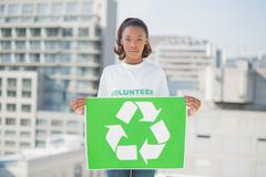 Serious volunteer woman holding recycling sign - stock photo