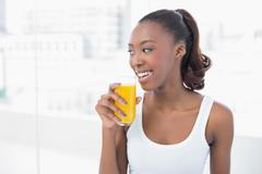 Stock Photo of Cheerful sporty model holding glass of orange juice
