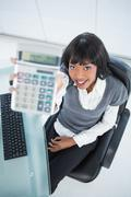 High angle view of smiling businesswoman showing calculator Stock Photos