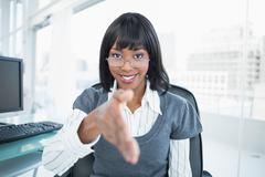 Stock Photo of Smiling gorgeous businesswoman offering hand