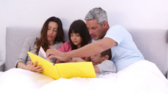 Family reading a storybook in the bed Stock Footage