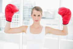 Competitive fit woman with red boxing gloves cheering up - stock photo