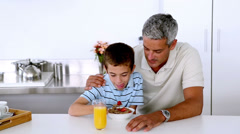 Father teasing son while he is having his breakfast Stock Footage