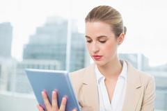 Stock Photo of Focused attractive businesswoman using her tablet