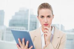 Stock Photo of Serious attractive businesswoman using her tablet