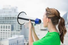 Side view of woman using megaphone Stock Photos