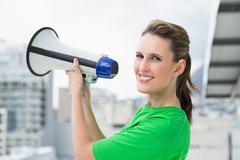 Smiling woman holding megaphone - stock photo