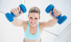 Cheerful blonde woman exercising with dumbbells - stock photo