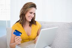 Pretty blonde using her credit card to buy online - stock photo