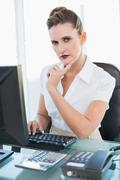 Thoughtful pretty businesswoman working on computer Stock Photos