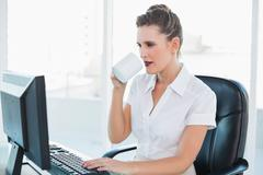 Attractive businesswoman drinking coffee and working on computer Stock Photos