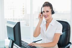 Happy call centre agent sitting on swivel chair Stock Photos