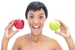 Stock Photo of Cheerful black haired woman holding apples