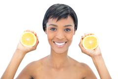 Pleased black haired woman holding two halves of an orange - stock photo