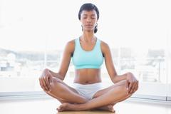 Meditative black haired woman doing yoga - stock photo