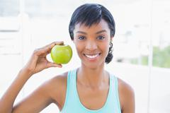Attractive black haired woman holding an apple - stock photo