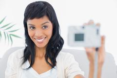Natural black haired woman in white clothes taking a picture of herself Stock Photos