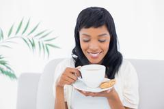 Stock Photo of Relaxed black haired woman in white clothes drinking coffee