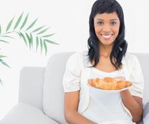 Stock Photo of Charming black haired woman in white clothes holding a croissant
