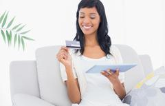 Delighted black haired woman buying online with her tablet pc - stock photo