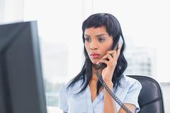 Frowning businesswoman answering the telephone Stock Photos