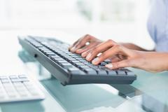 Stock Photo of Close up of a businesswoman typing on a keyboard