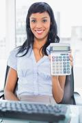 Delighted businesswoman holding a calculator Stock Photos
