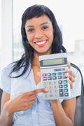 Amused businesswoman holding a calculator - stock photo