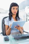 Stern businesswoman using a tablet pc - stock photo
