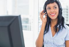 Attractive operator adjusting her headset - stock photo