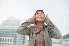 Troubled young model in winter clothes clogging her ears Stock Photos