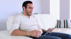 Handsome man using his tablet pc relaxing on his sofa Stock Footage