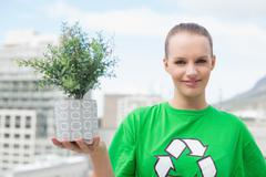 Happy pretty environmental activist showing a plant Stock Photos