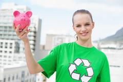 Content pretty environmental activist holding a piggy bank Stock Photos