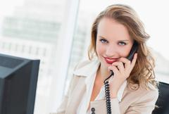 Cheerful pretty businesswoman answering a phone call Stock Photos