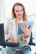 Calm pretty businesswoman using a tablet pc - stock photo