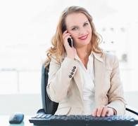 Pleased pretty businesswoman answering a phone call Stock Photos