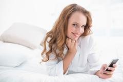 Amused pretty woman using her mobile phone on her bed - stock photo