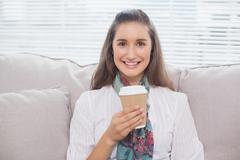 Smiling pretty model holding mug of coffee - stock photo
