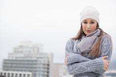 Stock Photo of Shivering cute brunette with winter clothes on posing