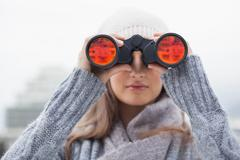 Cute woman with winter clothes on looking through binoculars - stock photo