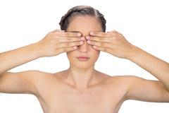 Unsmiling woman hiding her eyes - stock photo