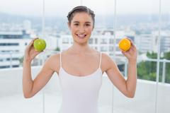 Stock Photo of Cheerful sporty brunette holding apple and orange