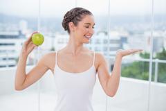 Happy sporty brunette holding green apple - stock photo