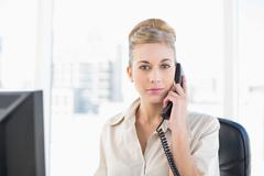 Stern young blonde businesswoman answering the telephone - stock photo