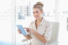Pleased young blonde businesswoman using a tablet pc Stock Photos