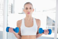 Attentive young blonde model exercising with dumbbells - stock photo